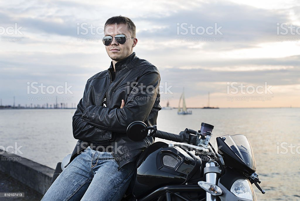Handsome young man in leather jacket on motorcycle on sunset light on...