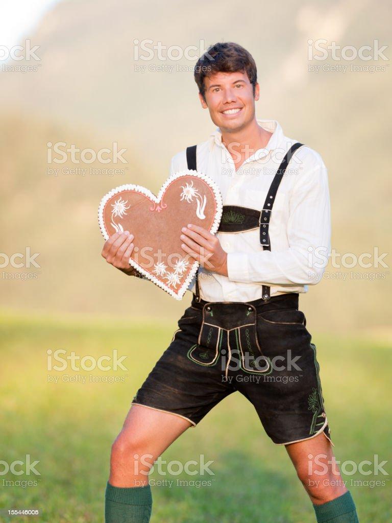Handsome Man in Lederhose holding a Gingerbread Heart (XXXL) stock photo