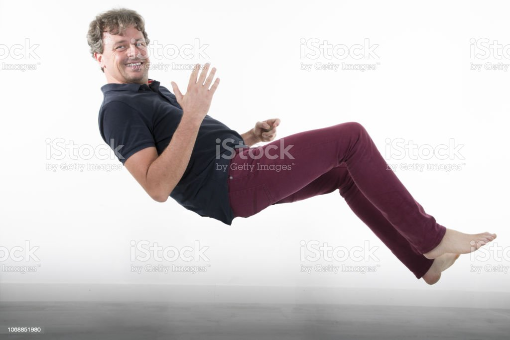 handsome man in levitation falling floating up at home in house white...