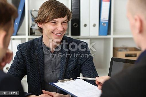 863148614istockphoto Handsome man in suit offer contract form on clipboard pad 801300206