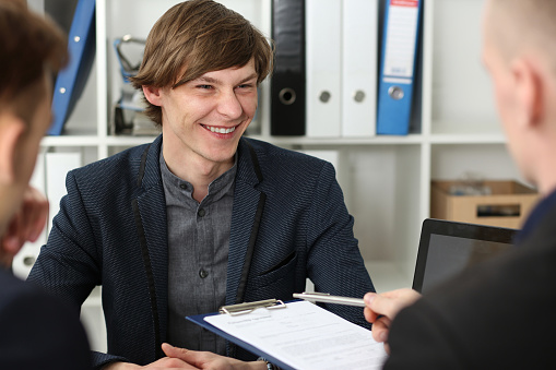 863148614 istock photo Handsome man in suit offer contract form on clipboard pad 801300206