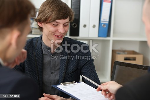 863148614istockphoto Handsome man in suit offer contract form on clipboard pad 841155184