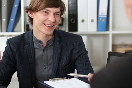 863148614 istock photo Handsome man in suit offer contract form on clipboard pad 841155202