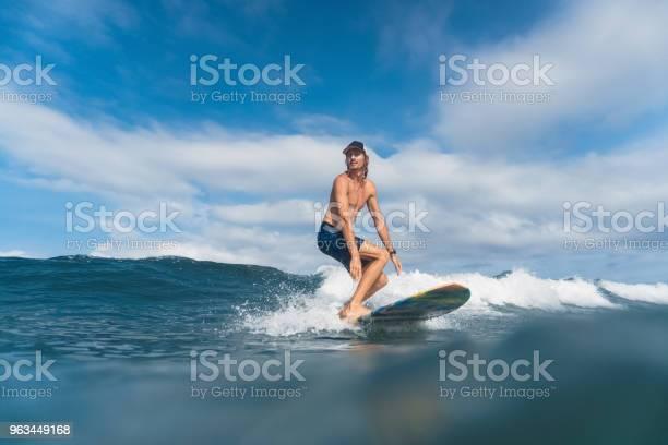 Przystojny Mężczyzna W Szortach Kąpielowych I Surfowaniu Po Oceanie - zdjęcia stockowe i więcej obrazów Bali