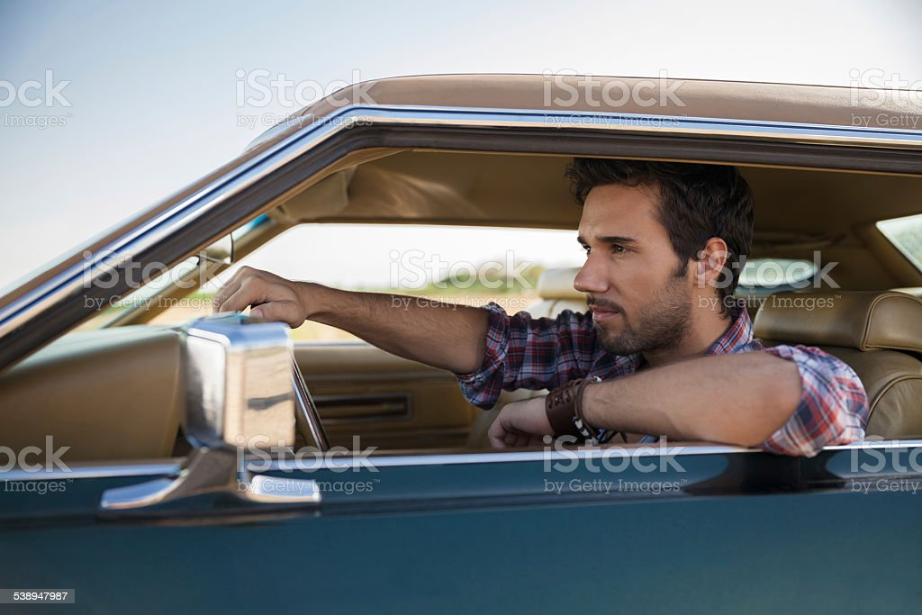 Close up of a handsome young man resting in his car