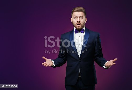 istock Handsome man in tuxedo and bow tie is surprised, throws 640231504