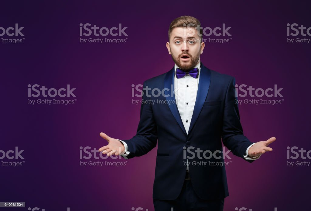 Handsome man in tuxedo and bow tie is surprised, throws stock photo