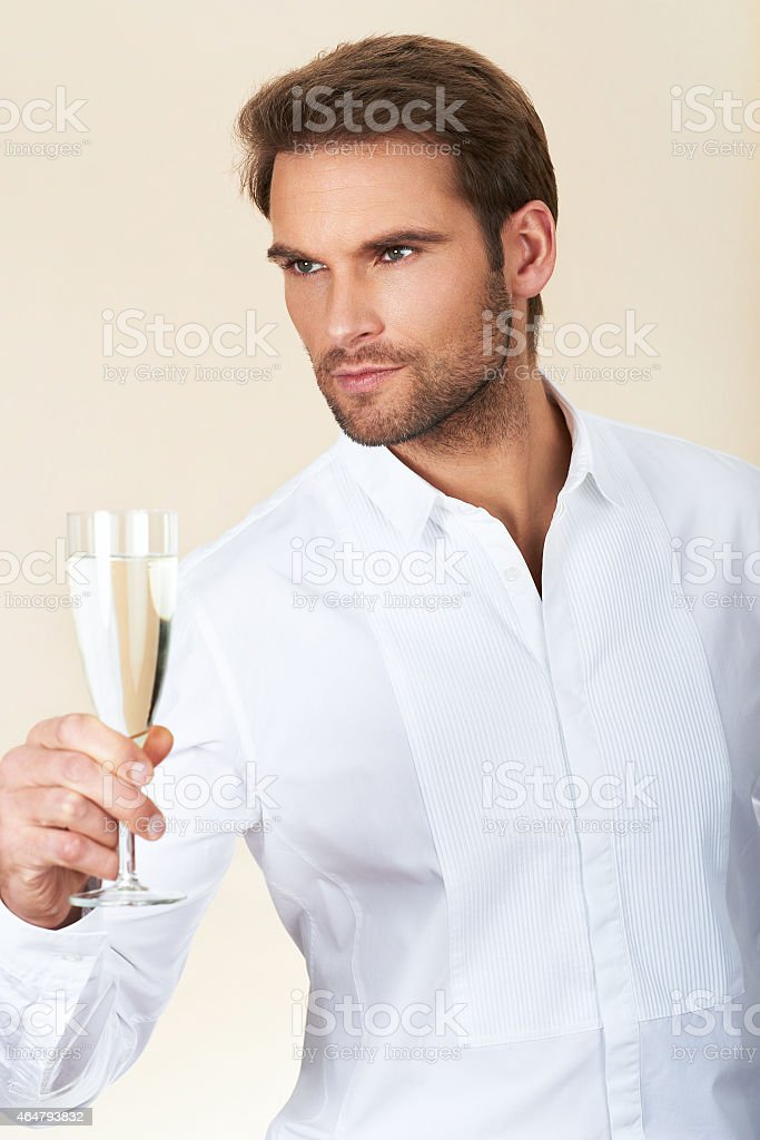 Handsome man in white shirt celebrating with glass of champagne Young businessman holding glass of champagne 2015 Stock Photo