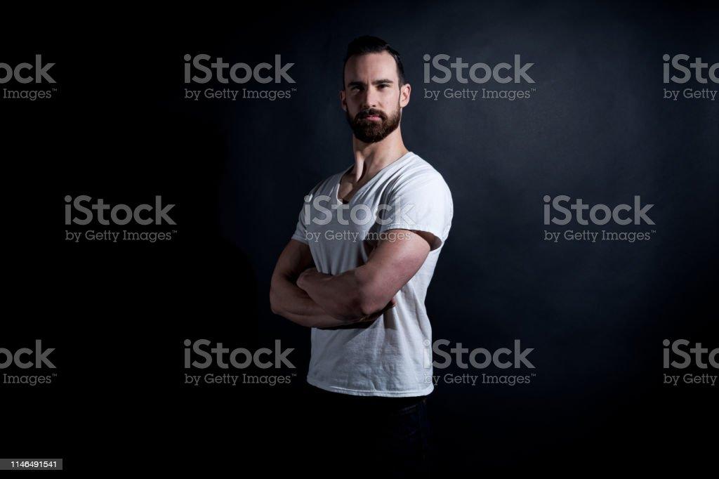 Handsome man in white tshirt on black background