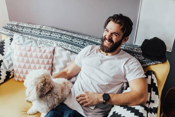gut aussehender mann im weißen t-shirt im sofa sitzen - freundin tattoos stock-fotos und bilder