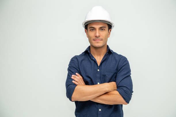 guapo hombre ingeniero industrial con un casco blanco consollado sobre fondo blanco - ingeniero fotografías e imágenes de stock