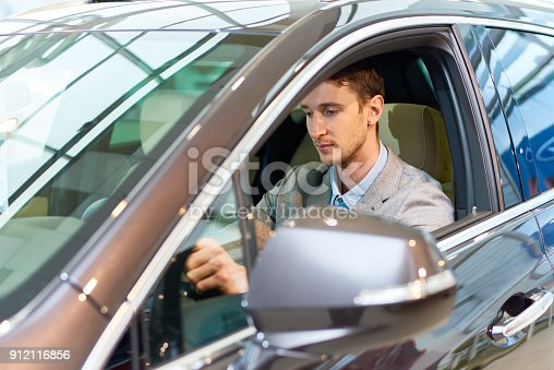 939005154 istock photo Handsome Man Inside New Car 912116856