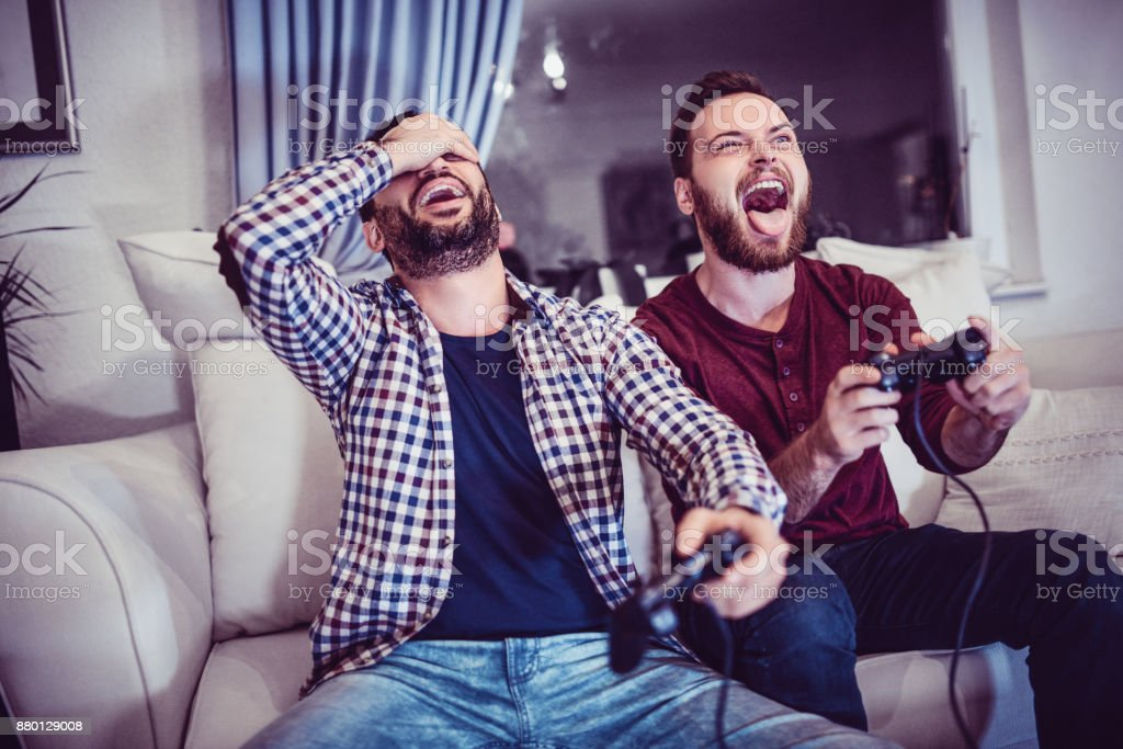 Handsome Man Is Defeating His Older Brother in Video Games stock photo