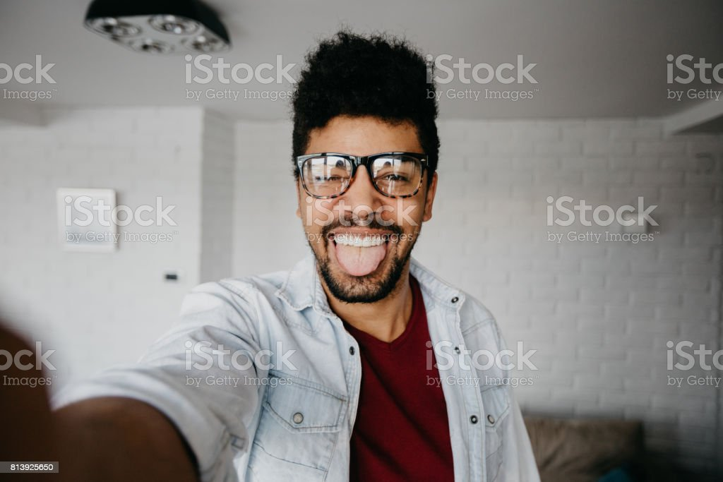 Handsome man is fooling around while doing selfie stock photo