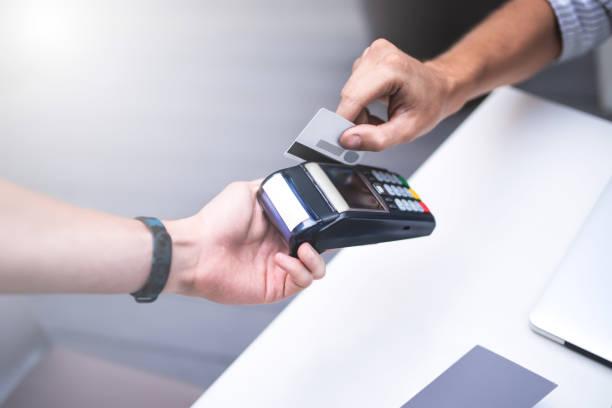 knappe man geeft een credit card in city café. - luchthaventerminal stockfoto's en -beelden