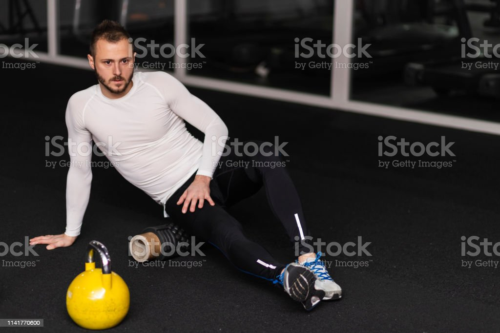 Portrait of a fitness man doing stretching exercises at gym using...