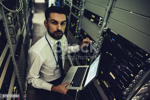 1170082011 istock photo Handsome man is working in data centre with laptop. 879720044