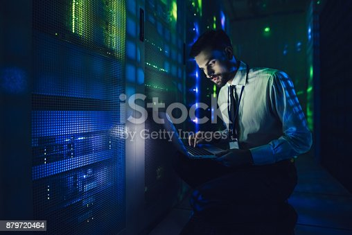 917307226istockphoto Handsome man is working in data centre with laptop. 879720464