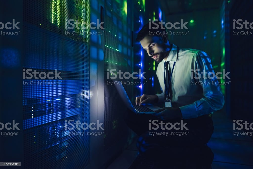 Handsome man is working in data centre with laptop. stock photo