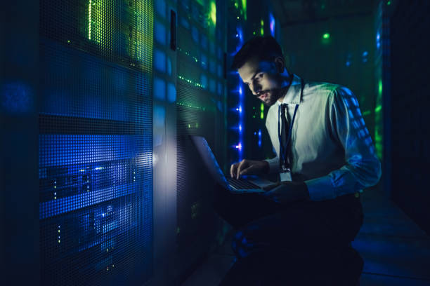 handsome man is working in data centre with laptop. - mainframe stock pictures, royalty-free photos & images