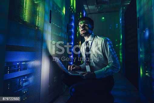 917307226istockphoto Handsome man is working in data centre with laptop. 879722532