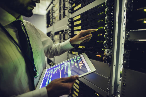 handsome man is working in data centre with tablet. - network server stock pictures, royalty-free photos & images