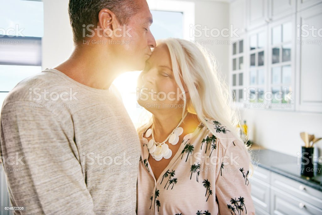 Handsome man kissing wife on forehead - foto de stock