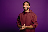 Portrait of a handsome Asian man wearing a purple hoodie standing in front of a purple background.
