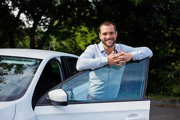 Handsome man leaning on car door stock photo