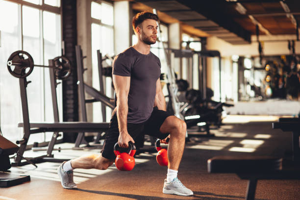Handsome man legs workout with kettlebell in the gym stock photo