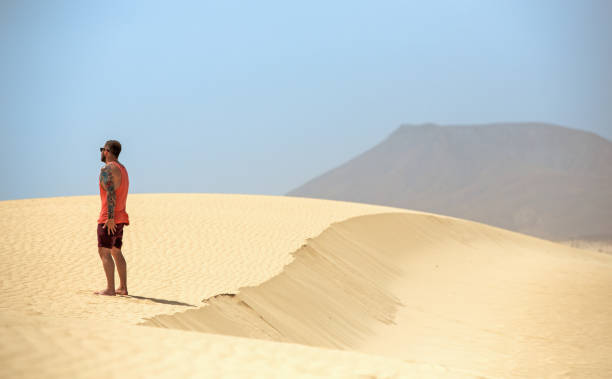 A handsome man looking at the horizon while standing on the sand dunes, in Fuerteventura, Canary islands, Spain stock photo