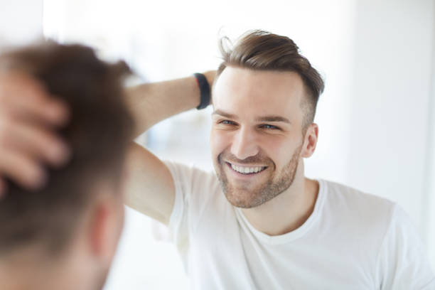 Handsome Man Looking in Mirror Portrait of handsome young man with lush hair and short stubble looking at his reflection in mirror and smiling, copy space hair stubble stock pictures, royalty-free photos & images