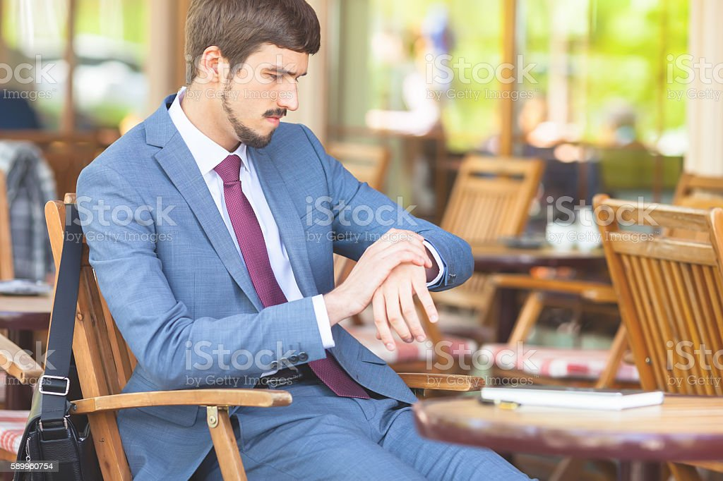 Handsome man looking time at watch stock photo