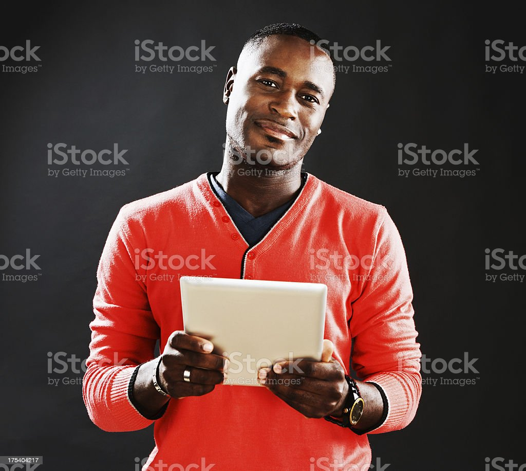 Handsome man looks up smiling from digital tablet stock photo