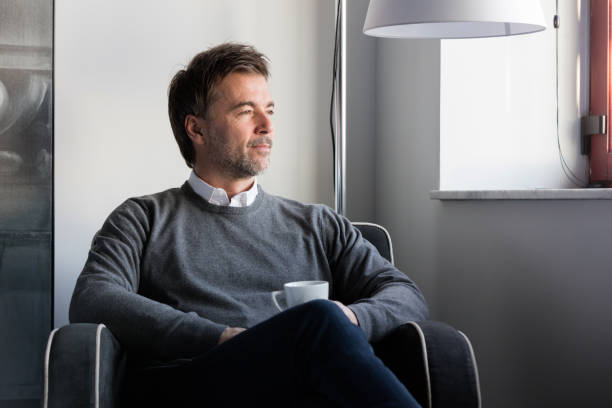 Handsome man lost in thought. He's serious. Relaxing. Having a coffee. stock photo