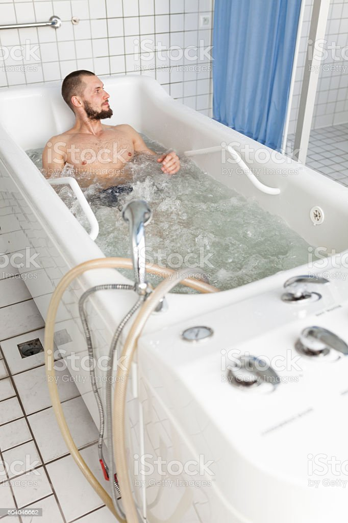 Handsome Man Lying In Hydromassage Tub stock photo