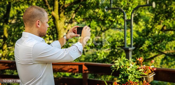istock Handsome man - Man standing - Businessman - A businessman makes pictures by phone 1015871186