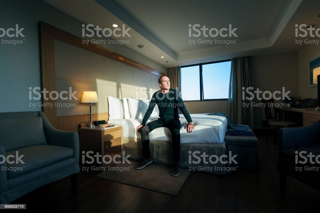 Handsome man on a hotel room stock photo