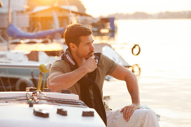 Handsome man on a sailing boat in sunset – Foto