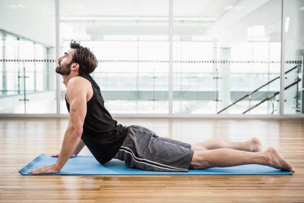Handsome man on cobra pose on the mat Handsome man on cobra pose on the mat in the studio cobra pose stock pictures, royalty-free photos & images