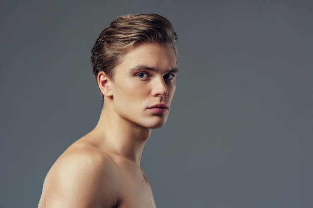 Handsome man on grey background. Handsome young man isolated. Portrait of shirtless muscular man is standing on grey background and looking at camera. shirtless male models stock pictures, royalty-free photos & images