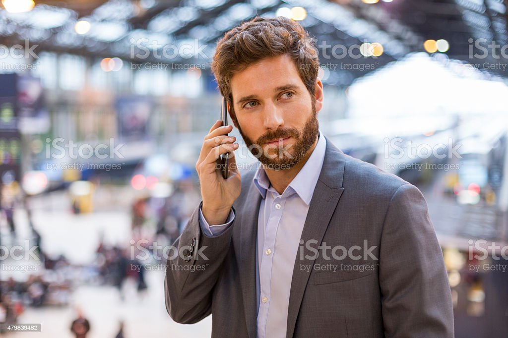 Handsome man on the mobile phone in hall station stock photo