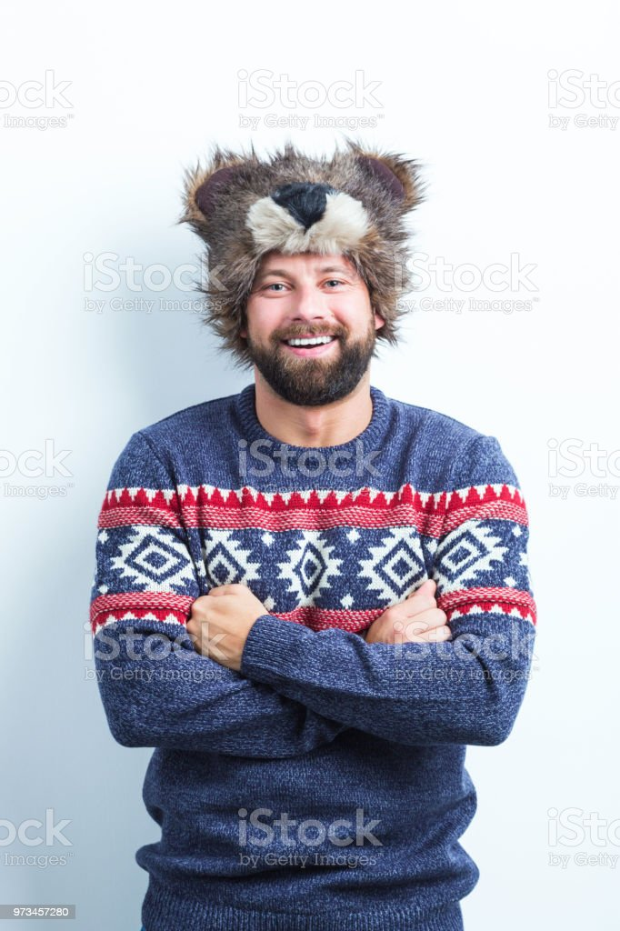 Handsome man on warm clothing Vertical portrait of handsome young man in warm clothing standing with his arms crossed on white background Adult Stock Photo