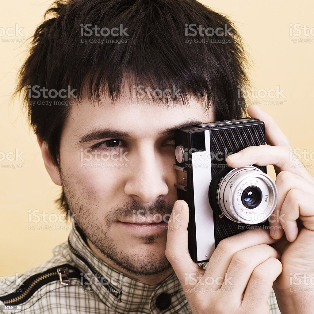 Handsome man photographing using vintage camera. Photographer royalty-free stock photo