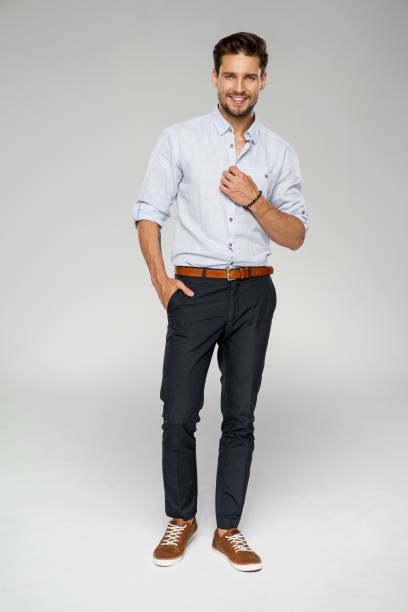 Handsome man Handsome man wear blue shirt and posing in studio hands in pockets stock pictures, royalty-free photos & images