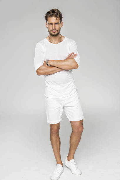 Handsome man Handsome male model with arms crossed wear white clothes shorts stock pictures, royalty-free photos & images