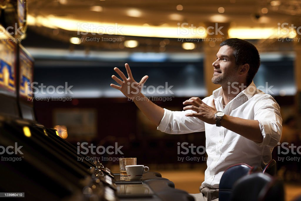 handsome man playing the slot machine stock photo