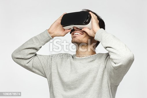 1090878574istockphoto Handsome man playing video games in VR goggles or 3d glasses, wearing virtual reality headset for on his head 1090878574