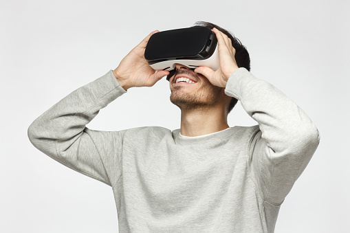 Handsome man playing video games in VR goggles or 3d glasses, wearing virtual reality headset for on his head