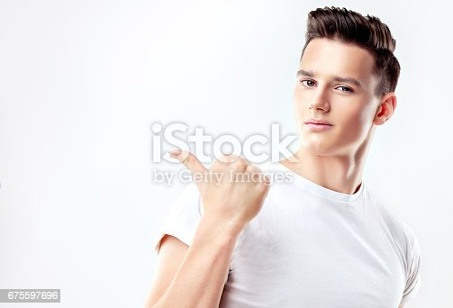 istock Handsome man pointing aside on invisible product. 675597696